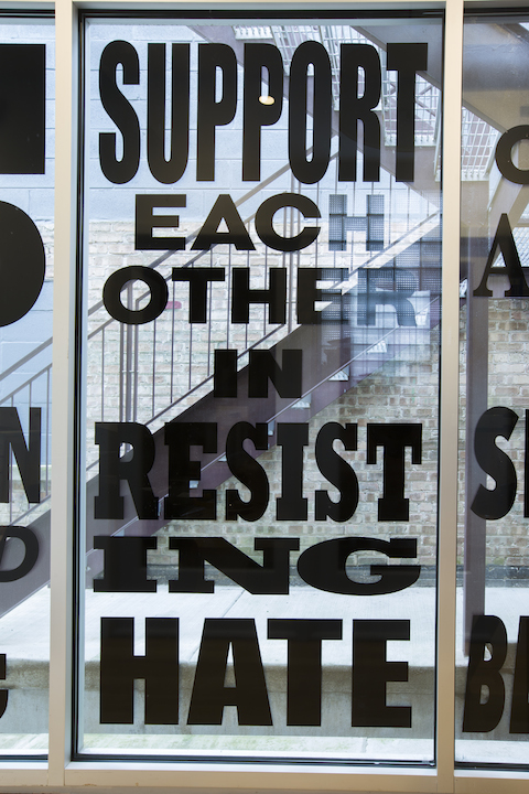 "Lisa Vinebaum, ""SUPPORT EACH OTHER IN RESISTING HATE,"" 2017. Custom cut vinyl window installation, 45x91.25 inches. Photo by Clare Britt."