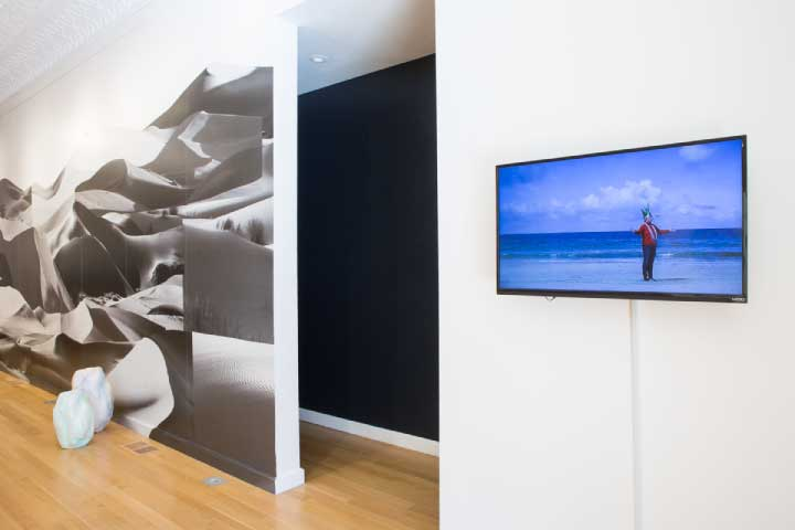 """Coming of Age,"" Installation view, Sector 2337, Chicago, 2017. Left: Rhonda Holberton, ""A FIXED RESISTANCE."" Pigment Print on Wallcovering, 12.5 x 55''. Right: Essi Kausalainen, ""Anette and Marin at the beach,"" 2017. HD video, 7 min. Photo by Clare Britt."
